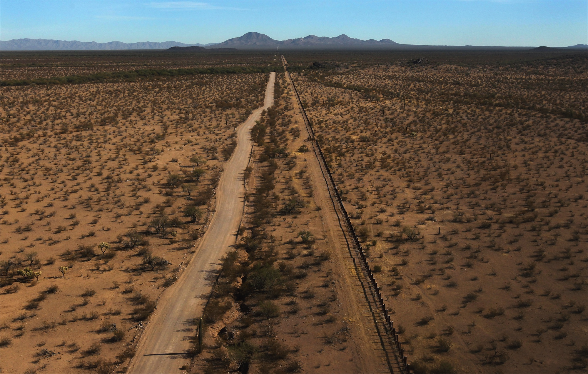 The U S Mexico Border Fence Through The Sonoran Desert In The Tohono O